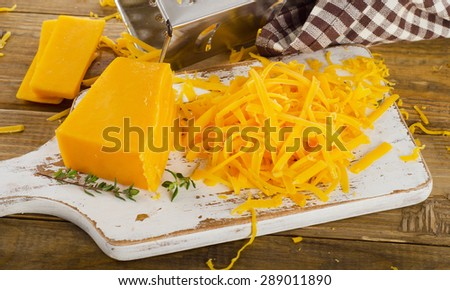 Cheddar Cheese on  a white wooden cutting Board. Selective focus - stock photo