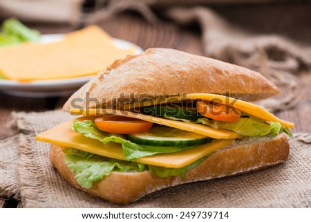 Cheddar Sandwich (close-up shot) with fresh salad on wooden background - stock photo