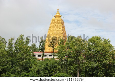 Chedi Buddhakhaya, built to mimic the Mahabodhi stupa of Bodhgaya in India, is a symbol of Sangklaburi,Thailand. It has hundreds of small metal Buddha images placed amid the corn-dob exterior. - stock photo