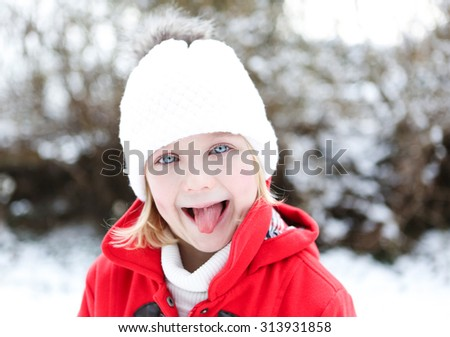 Cheecky girl in a snowy winter sticks her tongue out