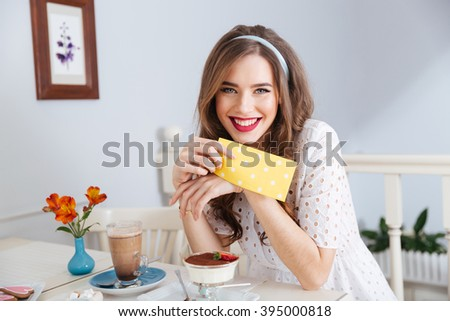 Cheeerful attractive young woman in white dress drinking latte and eating dessert in cafe - stock photo