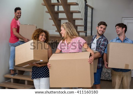 Cheeerful friends carrying cardboard boxes while relcocating in new house - stock photo