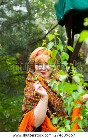 Cheeked Russian cheerful young woman in the green of spring foliage, with a scarf draped pavlopasadsky orange color with me-nots in hand, smiling pleasantly.