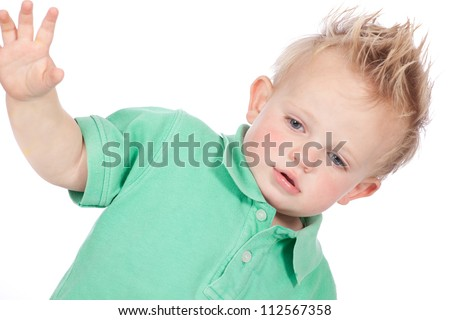 Cheeky and cute blond hair blue eyed baby boy in green polo shirt and spiky mohawk hairstyle - stock photo