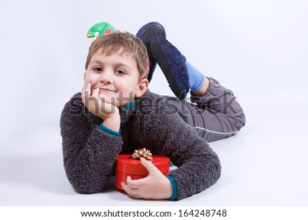 cheeky boy wearing elf's hat with a gift on white - stock photo