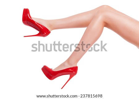 Cheeky heel. Close-up of young woman in high heeled shoes isolated on white  - stock photo