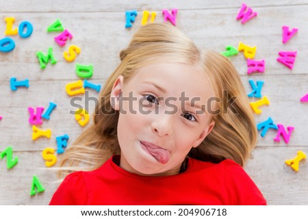 Cheeky little girl. Top view of cute little girl grimacing while lying on the floor with plastic colorful letters laying around her - stock photo