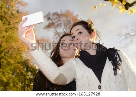 cheeky sisters with smartphone in autumn park - stock photo