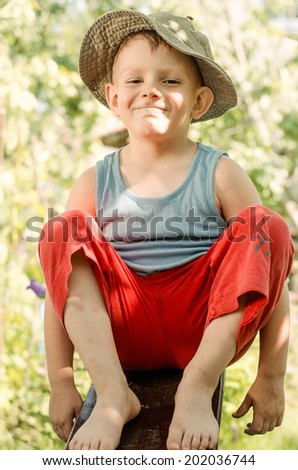 Cheeky young barefoot country boy in red pants and a t-shirt grinning playfully at the camera as he sits on a plank of wood in the garden - stock photo