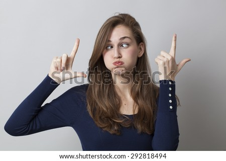 cheeky young girl making the LOL sign with humor for boring trends in hand gesture - stock photo