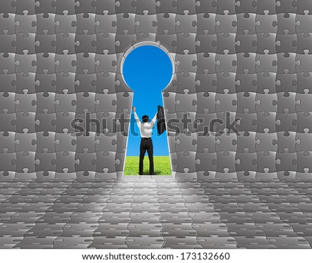 Cheered businessman standing outside puzzle building with key shape door and blue sky - stock photo