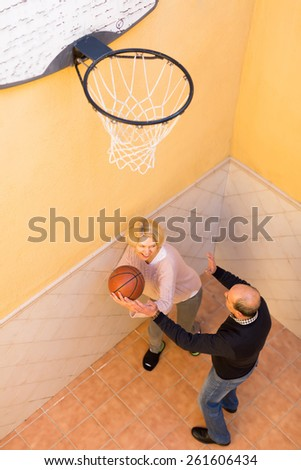 Cheerful active senior spouses playing basketball in patio - stock photo