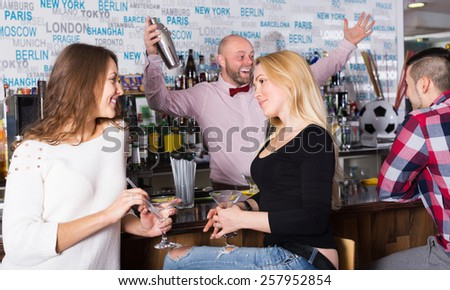Cheerful adult friends drinking and chatting with happy barman at bar counter - stock photo