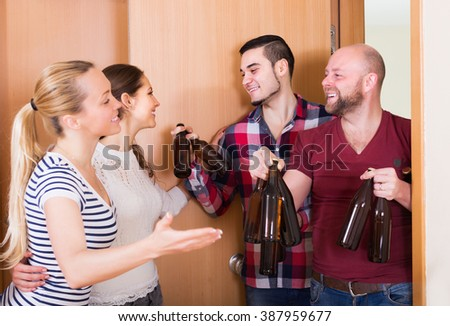 Cheerful adult friends gathering together at house booze party
