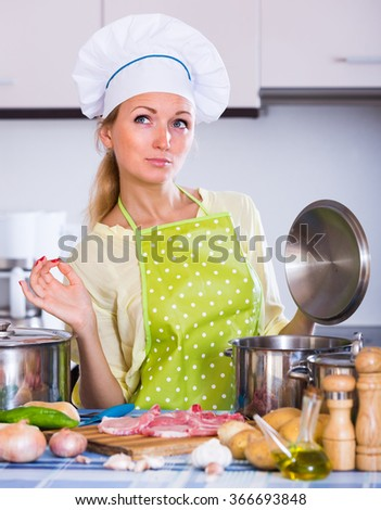 Cheerful adult girl cooking meat for dinner at home kitchen