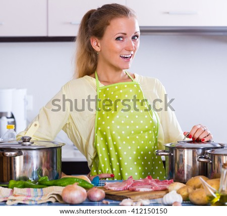 Cheerful adult girl in apron cooking meat for dinner at home kitchen