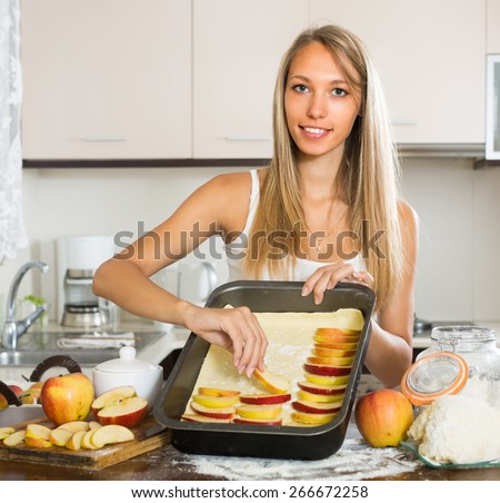 Cheerful adult girl preparing apple cake in kitchen - stock photo