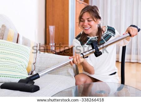 Cheerful adult girl vacuuming floor and furniture indoor - stock photo