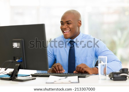 cheerful african american businessman working on computer - stock photo