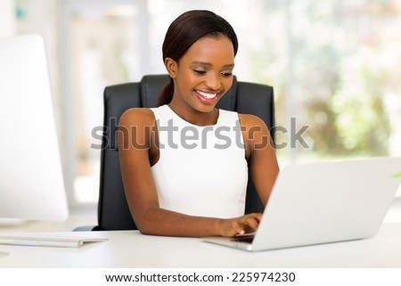 cheerful african american businesswoman using laptop in office - stock photo