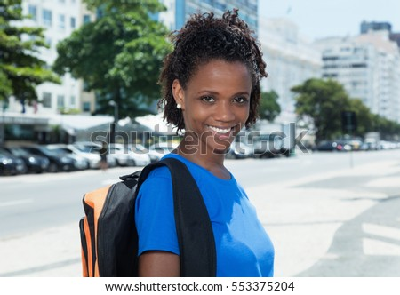 Cheerful african american female student in the city