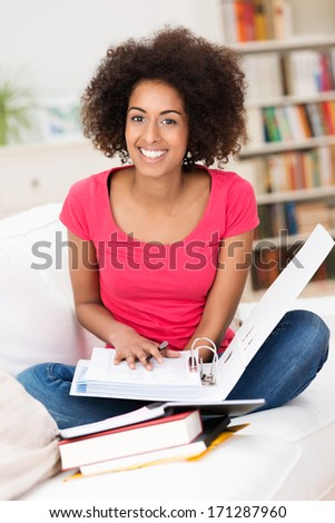 Cheerful African American female student, wearing casual clothes, sitting in the lotus position on the sofa, while holding an open folder and having different books in front of her - stock photo