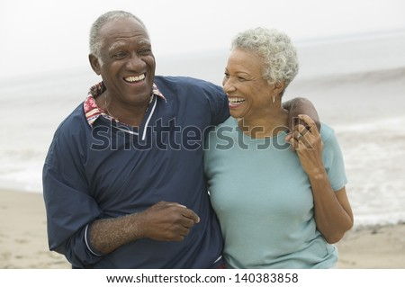 Cheerful African American mature couple with arms around at the beach - stock photo
