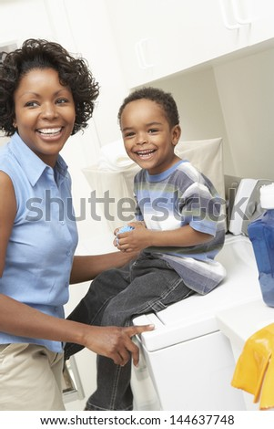 Cheerful African American mother and son in the laundry room - stock photo