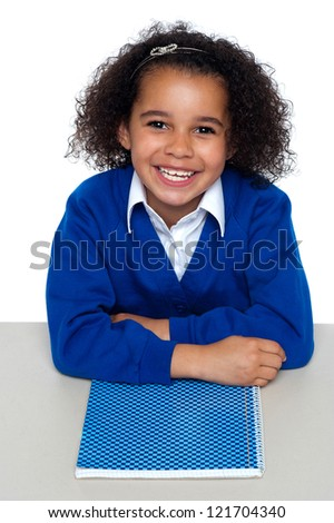 Cheerful African American relaxed student facing camera and smiling. Notebook beneath her crossed arms. - stock photo