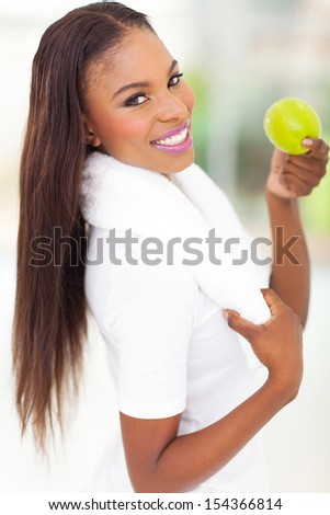 cheerful african american woman holding an apple after exercise - stock photo