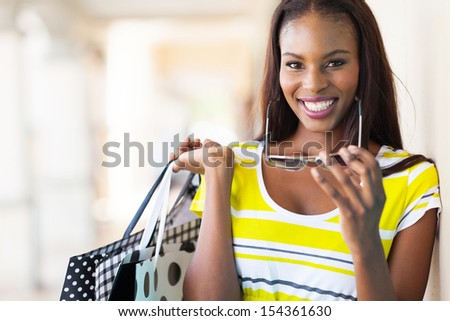 cheerful african american woman shopping in mall - stock photo
