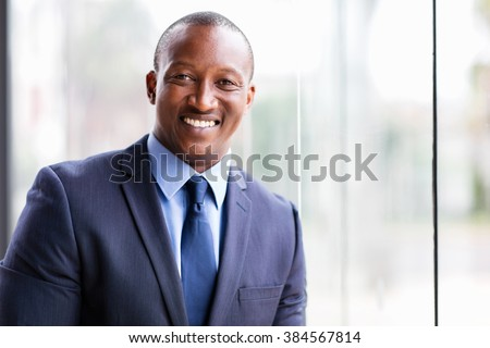 cheerful african business man standing by office window