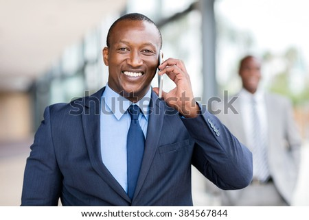 cheerful african businessman talking on cell phone in office - stock photo