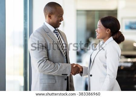 cheerful african car dealer handshake with customer in showroom - stock photo