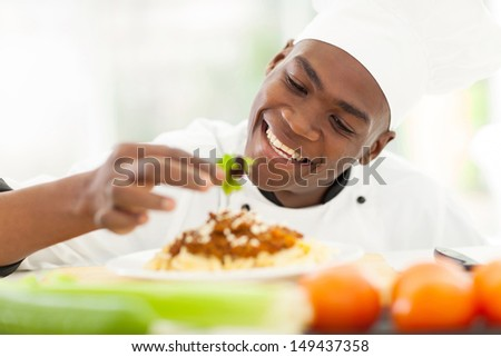 cheerful african chef decorating spaghetti - stock photo