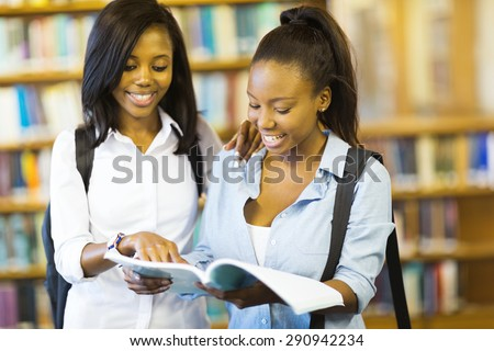 cheerful african college girls reading a book in library - stock photo