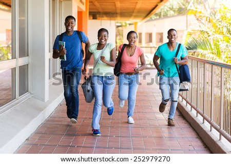 cheerful african college students running to lecture hall - stock photo