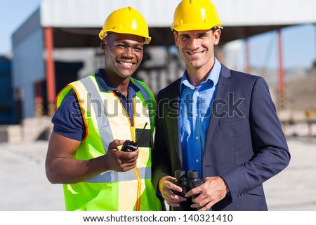 cheerful african construction worker and manager portrait outdoors - stock photo