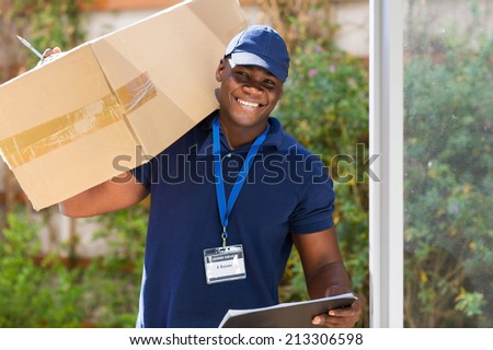 cheerful african courier standing with parcel at the door  - stock photo