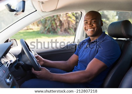 cheerful african man inside his new car - stock photo