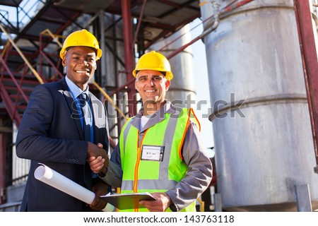 cheerful african refinery manager handshaking with senior worker in front of fuel-tanks - stock photo