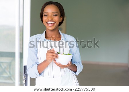 cheerful african vegetarian eating salad at home - stock photo