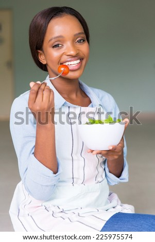 cheerful african woman eating healthy food - stock photo