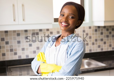 cheerful african woman standing in the kitchen - stock photo