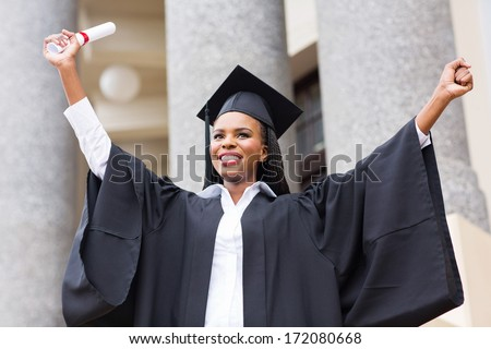 cheerful afro american female graduate standing in front of university building - stock photo