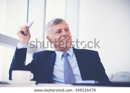 Cheerful aged businessman launching paper plane