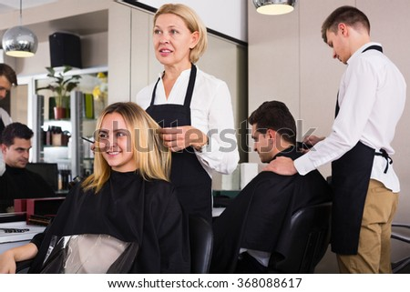 Cheerful aged woman cutting girl hair in the barbershop