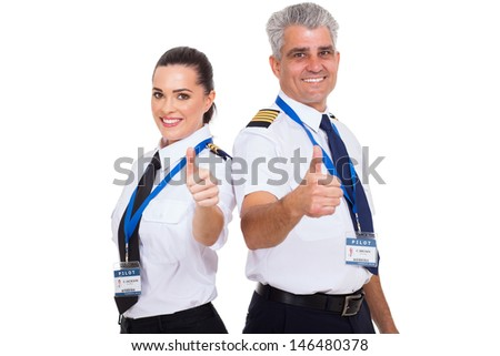cheerful airline pilots giving thumbs up over white background - stock photo