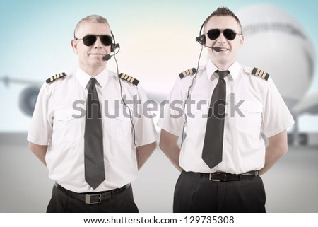 Cheerful airline pilots wearing uniforms with epauletes and headsets standing with airliner in background. - stock photo