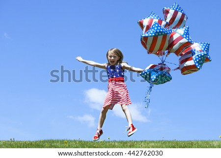 Cheerful American  girl with balloons jumping outside. 4th of July. Independence day.